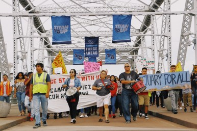 Participants in the silent march hold signs and walk the Pedestrian Walk Bridge in Nashville, Tenn. on Oct. 21, 2017. (Anthony Merriweather / MTSU Sidelines)