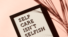 """A letterboard lays against a pink background: it says """"self-care isn't selfish"""""""