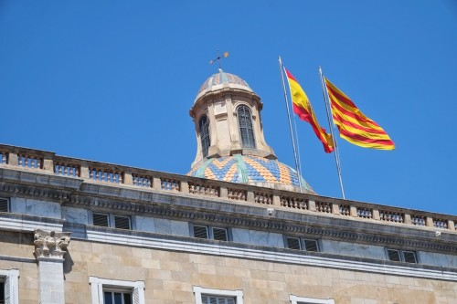Flags of Spain and Catalonia fly above a public building in Barcelona.