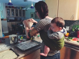 baby wearing and dinner making