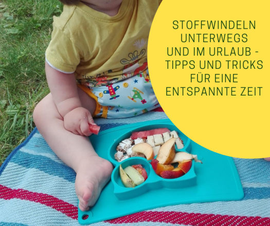 Kind in Stoffwindel beim Picknick