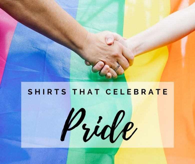 two arms holding hands in front of Pride flag