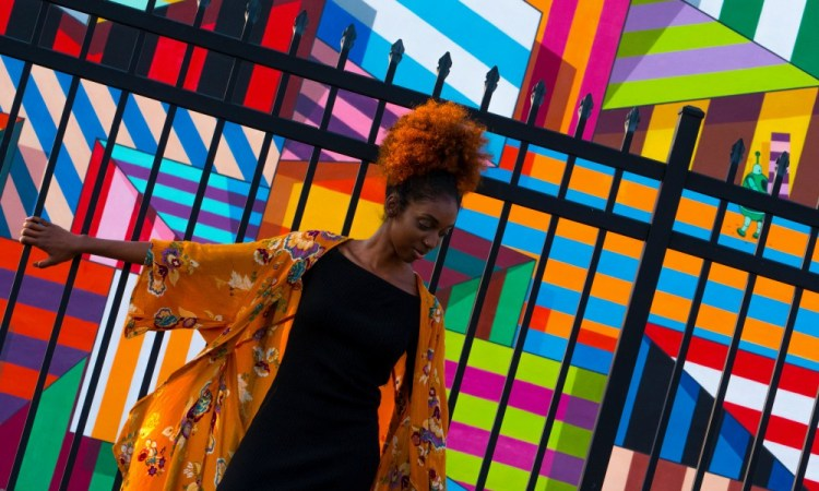 Centered. African-American woman leaning against a fence. Colorful mural