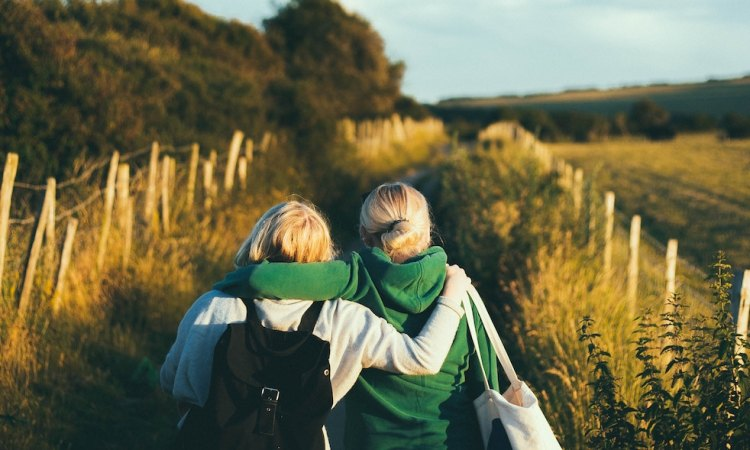 two women walking down a path in a meadow, their arms around each other's shoulders
