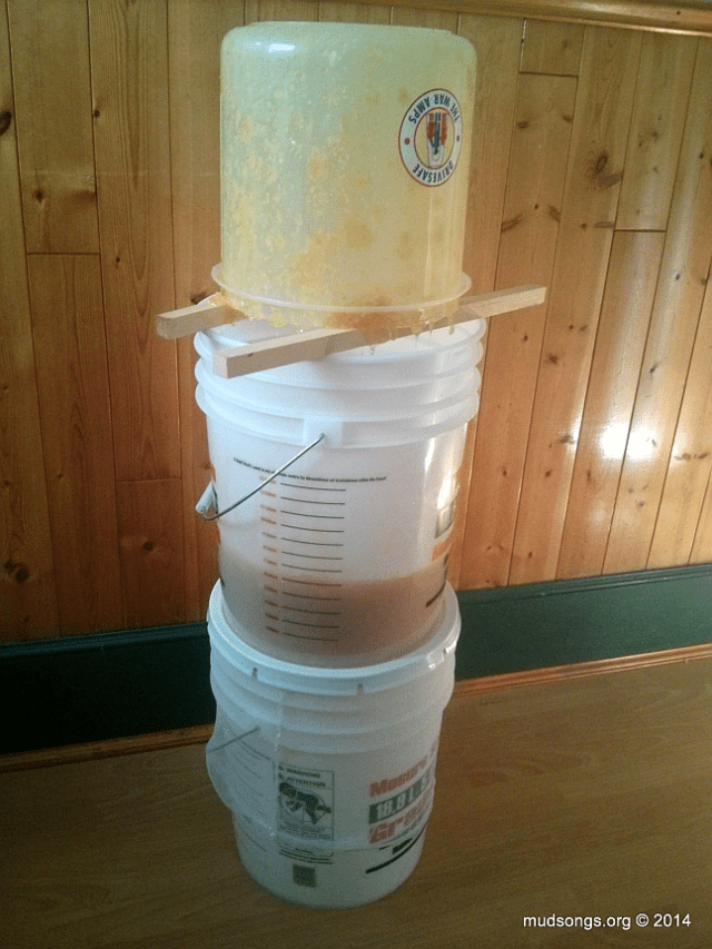 Honey with crushed comb dripping from top bucket into bucket with holes, then straining into bottom bucket. (Oct. 07, 2014.)