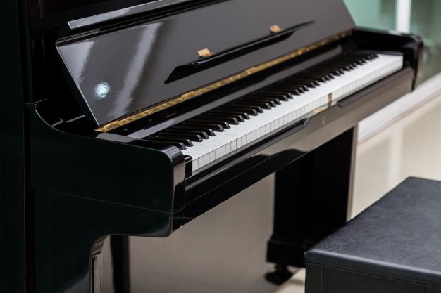 schoene-klavier-neben-einem-hocker_1232-350