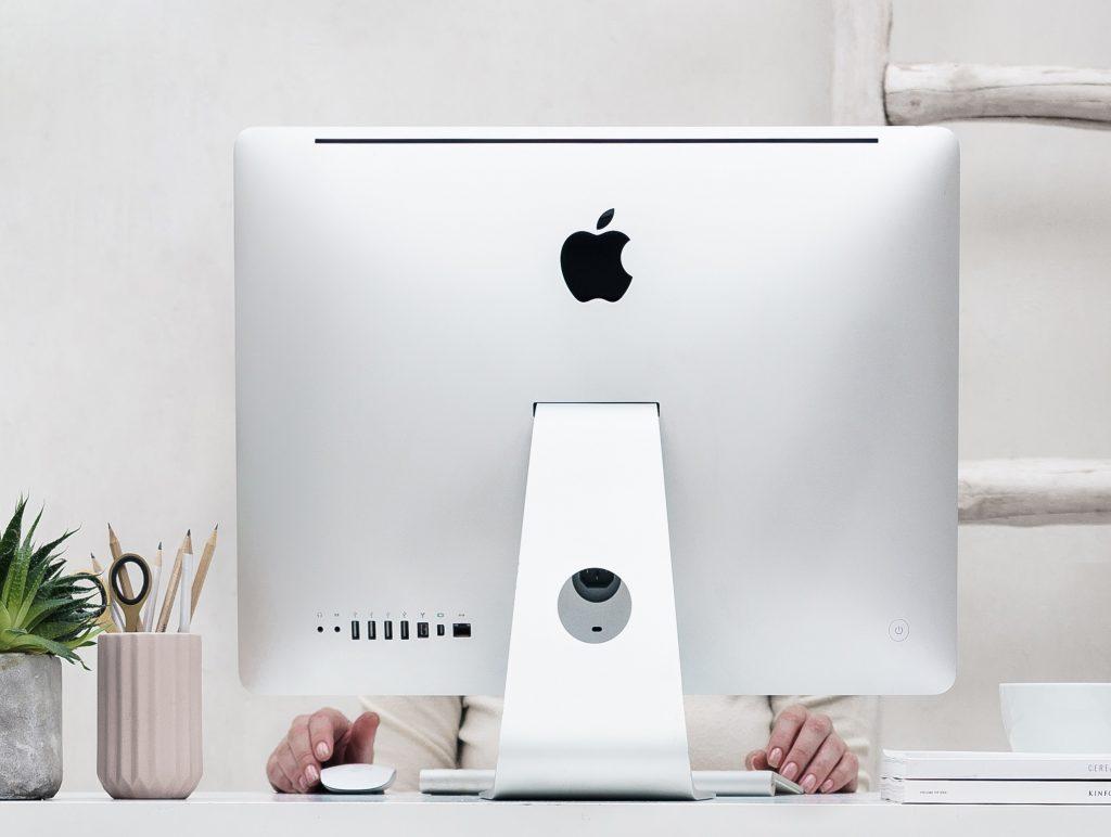 Startklar zum ersten Mal bloggen - Frauenhände schauen untre einem Bildschirm hervor, ein aufgeräumter Schreibtscih.