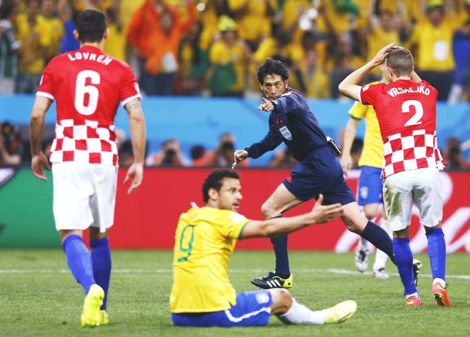Referee Yuichi Nishimura of Japan gestures for a penalty during the 2014 World Cup opening match between Brazil and Croatia at the Corinthians arena in Sao Paulo
