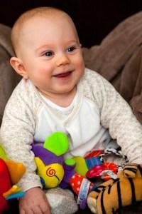 Smějící se kojenec s plyšovými hračkami