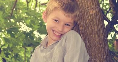 Na obrázku je smějící se chlapec s blond vlasy, modrýma očima a šedou košilí. Opírá se o strom.