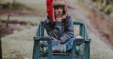 Na obrázku sedí dítě, které je ve vozíku. Má červenou beranici a smutně kouká stranou.