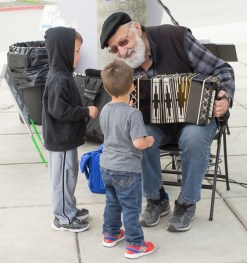 Polka Dan explains the concertina to a pair of young fans.