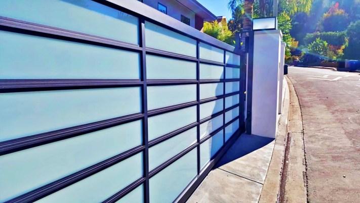 Black aluminum and blue glass driveway gate