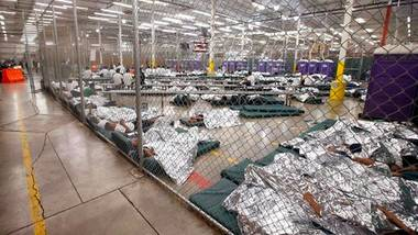 Children in cages sleeping in space blankets