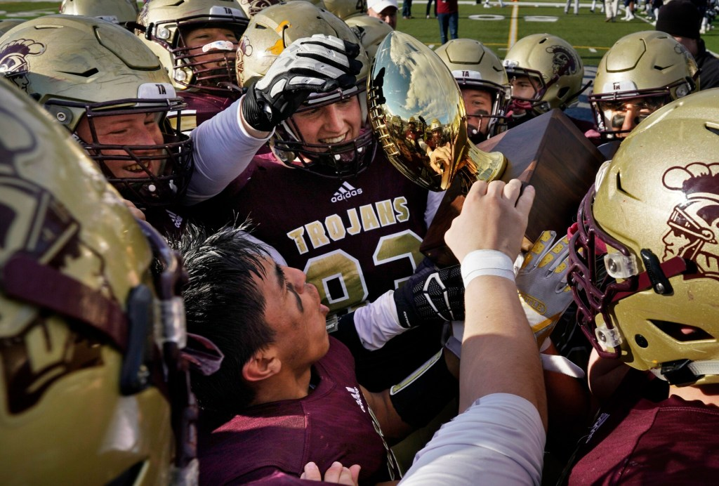 PORTLAND, ME - NOVEMBER 17: Ethan Logan, center and Anthony Bracamonte, below, and other Thornton Academy players hold the championship trophy while celebrating their 49-14 victory over Portland in the Class A Football state championship at Fitzpatrick Stadium in Portland on Saturday, November 17, 2018. (Staff photo by Gregory Rec/Staff Photographer)