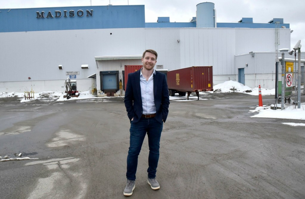 Josh Henry, of the Go Lab company, stands in front of the shuttered former UPM paper mill in Madison on April 10. Henry's company closed on the purchase of the mill last week and expects to hire 120 or more people to work there producing wood fiber insulation.
