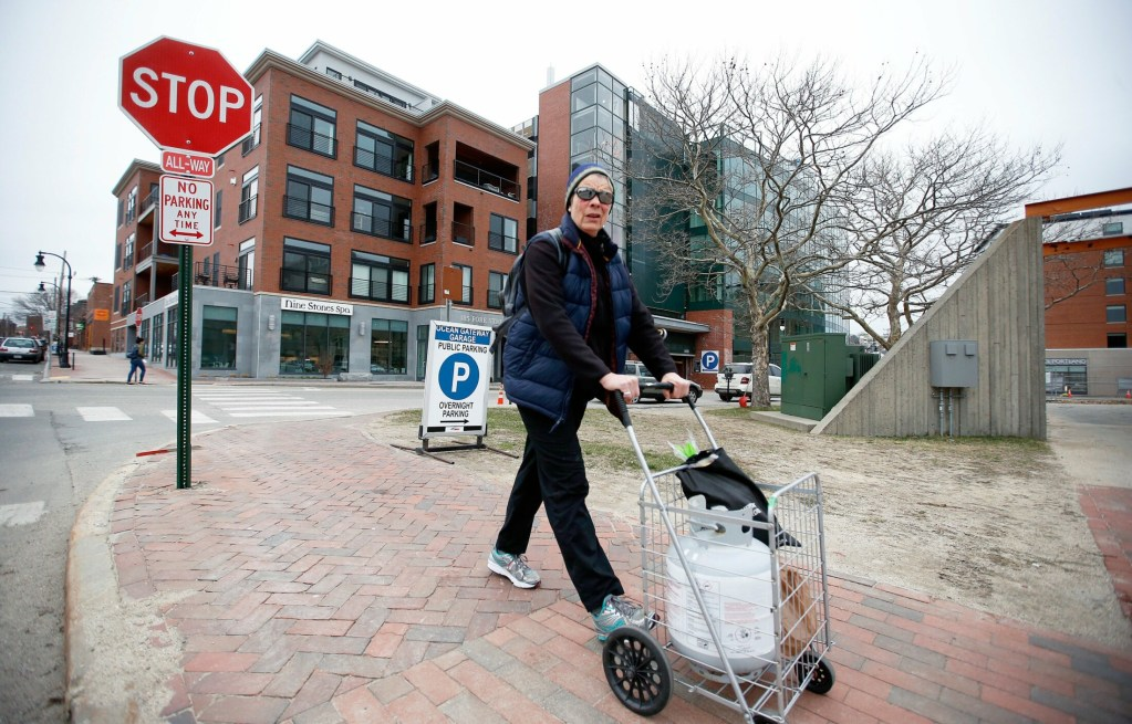 Peaks Island resident Molly Johnson pushes a cart last week from the Ocean Gateway Garage, where she has a monthly parking pass. Garage manager Unified Parking Partners had told some island residents last week that they would be evicted from their spaces, but said Friday that at least some of the residents would be allowed to keep their spaces.
