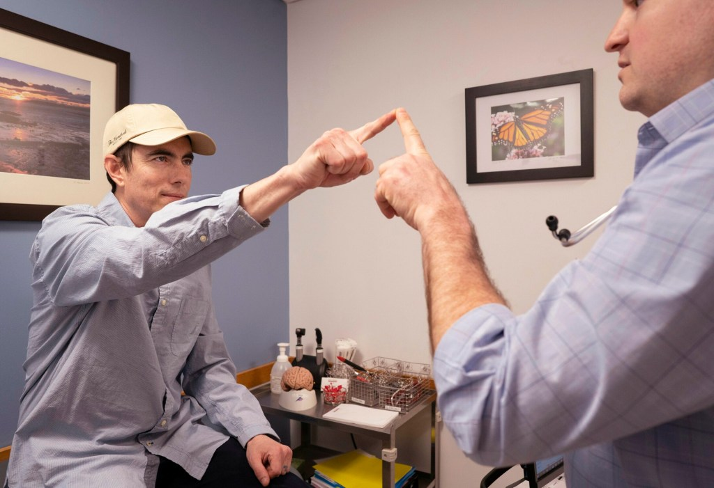 Gregory Francis touches the finger of physician assistant Sam Gagnon during a neurological examination at Maine Medical Partners in Scarborough on April 18. Francis had a brain tumor removed and is on medication prescribed based on a biopsy of the tumor done by Jackson Laboratory.