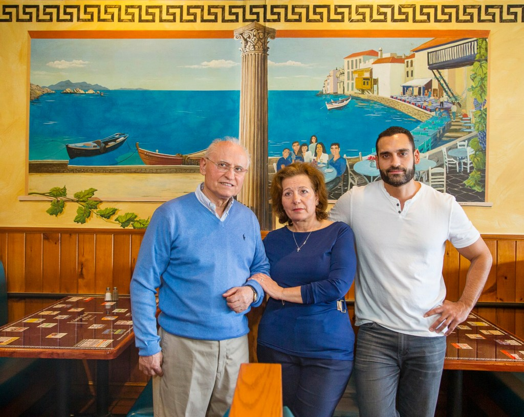 Owners of the Falmouth House of Pizza, Sotirios, Antonia and Lee Soritopoullos, stand in the dining area of their restaurant.