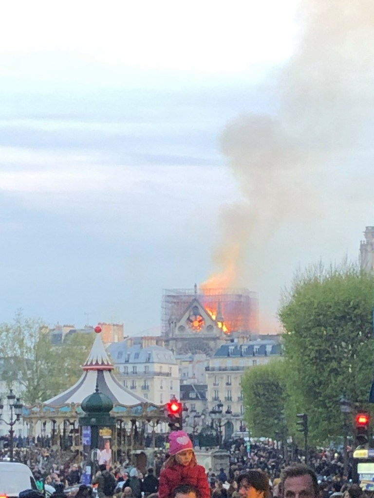 Crowds gather to watch efforts to knock down the flames at the Cathedral of Notre Dame in Paris Monday.