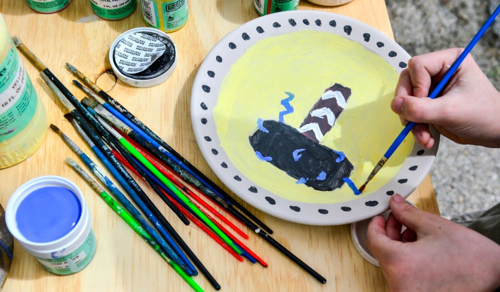 Eddie Schmidt, 11, of Chelsea, paints Thor's hammer onto a plate Saturday during a Maine Pottery Tour event at Fine Mess Pottery in Augusta.