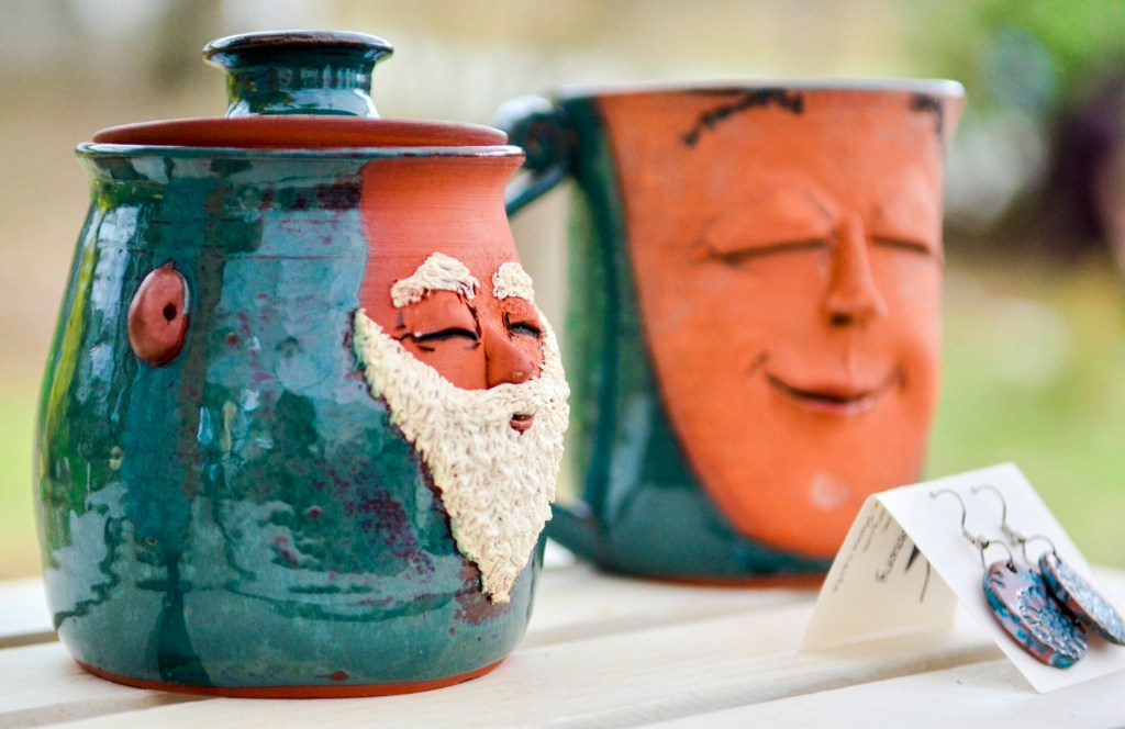 Face mugs made by guest artist Martha Hoddinott are offered for sale Saturday during a Maine Pottery Tour event at Fine Mess Pottery in Augusta.