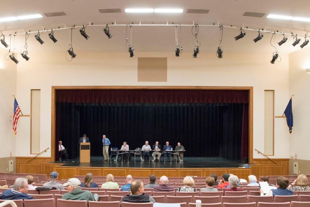 People gather Tuesday for the Oakland Town Meeting at the performing arts center at Messalonskee High School.
