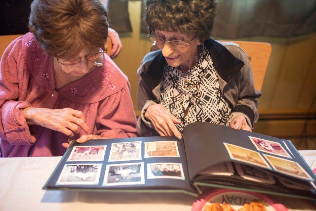 "Mary Pizzo McCarthy, left, and Amelia ""Millie"" Pizzo Lane look at old photo albums while celebrating their 100th birthday at Mary's home in Portland on Wednesday. The twins were born in Italy and immigrated to Portland with their parents in 1929."