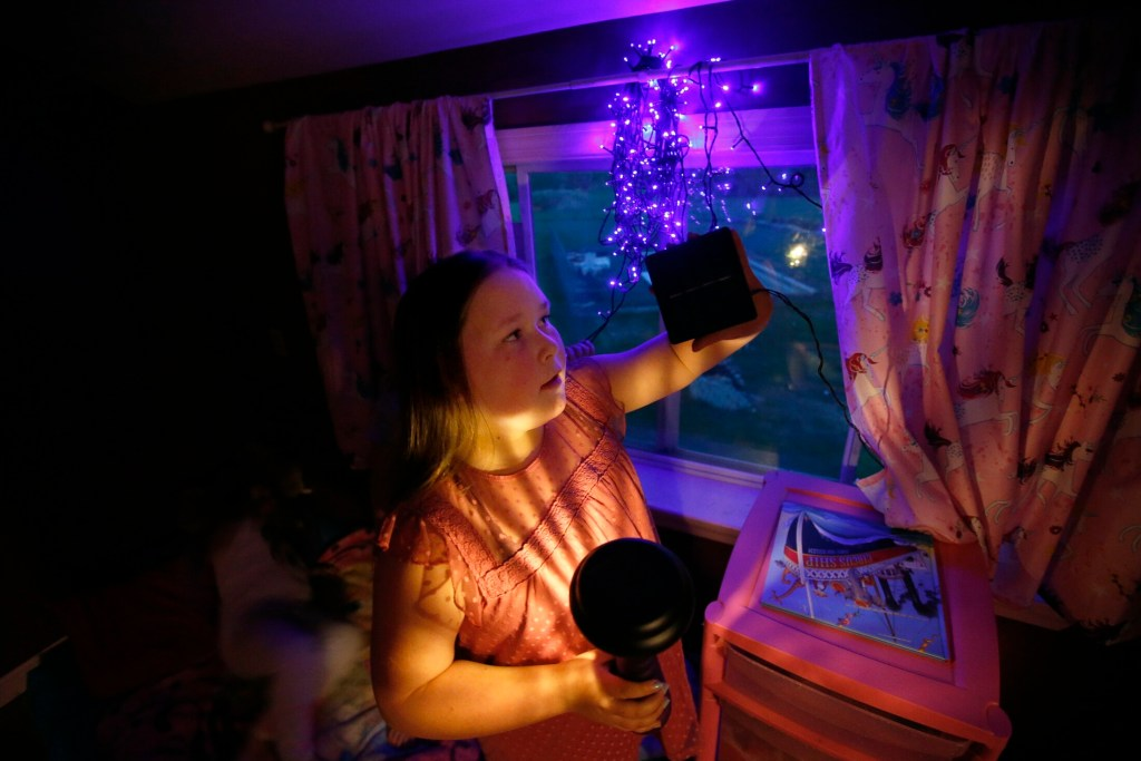 Sera Dixon, 9, holds a solar light in her right hand while demonstrating a solar panel with her left in the bedroom she shares with her twin sisters. The family has been using solar lights to cut down on electricity costs.