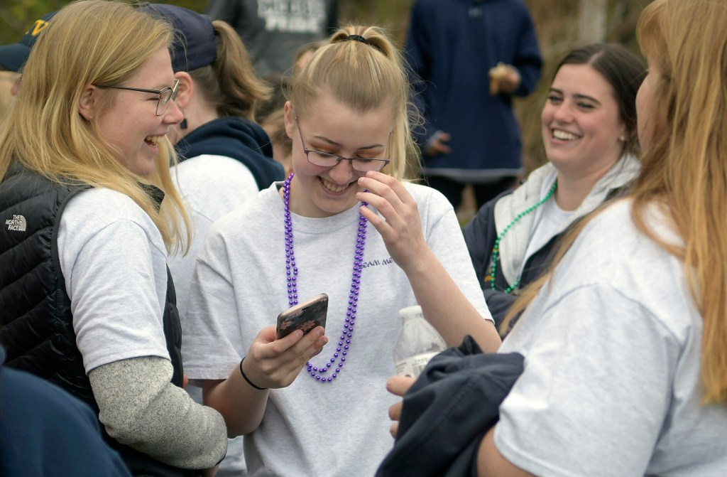 Melayna Benner, center, laughs with teammates from the Medomak Valley High School softball team who attended the Great Strides cystic fibrosis walk with her in Augusta on Sunday.