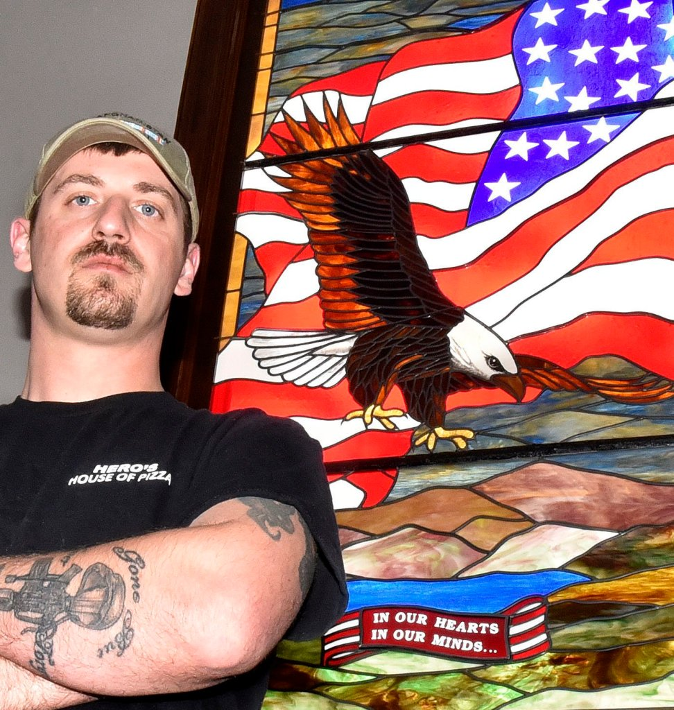 Veteran Derek DeFelice, standing on Wednesday before a patriotic-themed stained glass window in the Skowhegan Town Office, is the grand marshal for the Skowhegan Memorial Day parade this Monday.