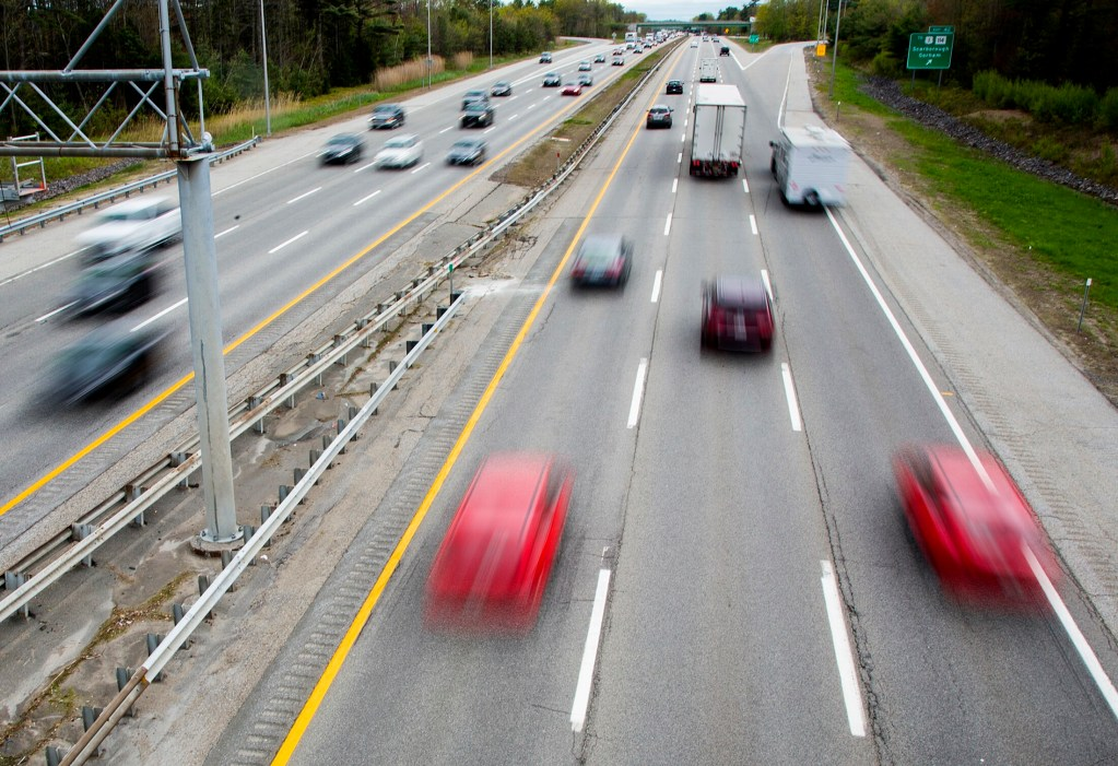 Steady traffic flows under the overpass near Exit 42 of the Maine Turnpike in Scarborough on Friday. The turnpike authority is projecting another record-breaking weekend for traffic.