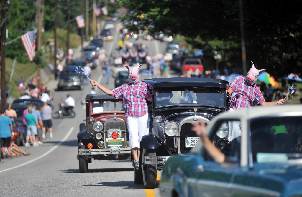Pat Knowlton, center, and Kathie Blodeau , right, hang from the Pat's Wallpaper antique car dressed as pigs with pinwheels in the Blueberry Festival parade on Main Street in downtown Wilton in August 2012.