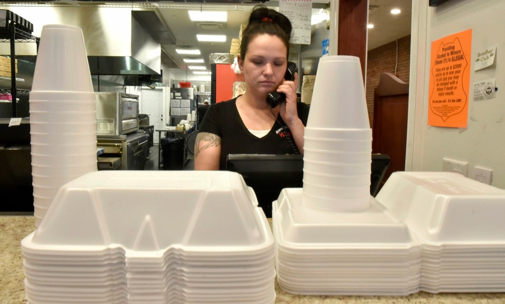 Waterville House of Pizza Manager Ashley Ann Ferris speaks on the phone near stacks of styrofoam products used for take-out orders on Thursday. Owner Stavros Kosmidis said he understands the benefit of banning plastic, but the cost is not ideal.