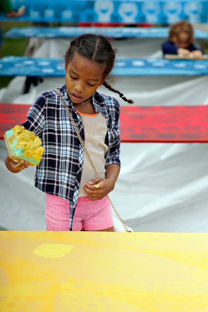 Jaiden Johnson, 9, of Portland removes a sponge to reveal a painted pattern during a TEMPOart event, led by Portland artist Daniel Minter in early June in Kennedy Park. The completed works will be part of a public art installation, Mother's Garden, beginning June 15 that link food, culture and art.