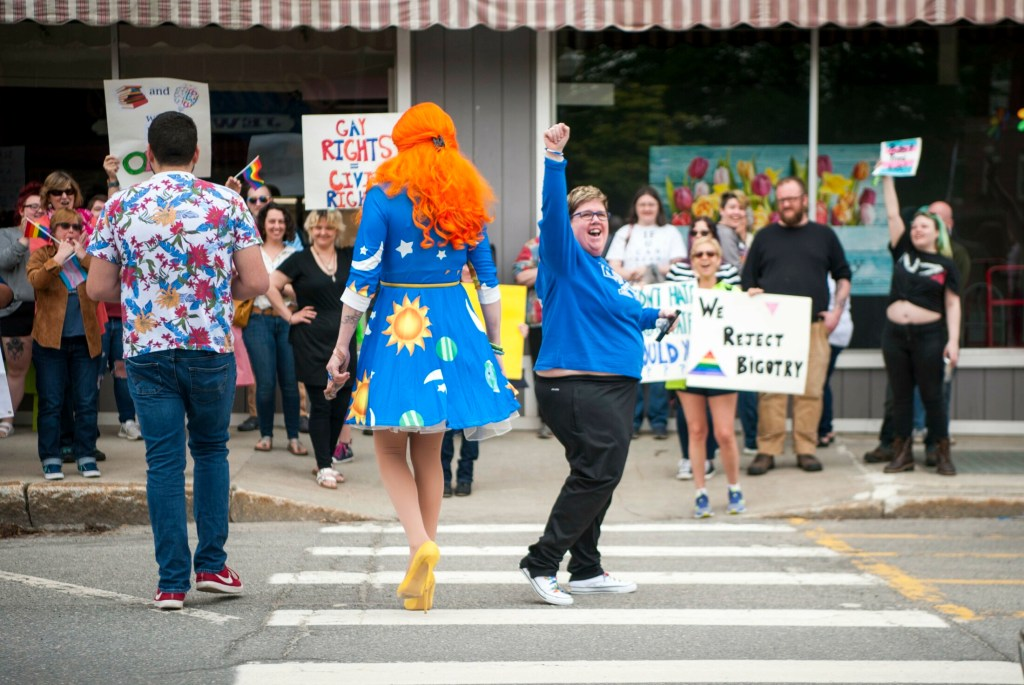Ophelia, a drag queen, crosses Main Street toward a group of activist promoting equality Saturday at the Children's Book Cellar in Waterville.