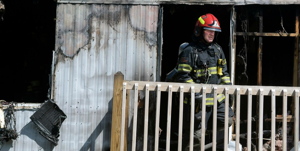 Captain Douglas Ebert of the Farmingdale Fire Department emerges Monday from a mobile home that burned in Randolph. An occupant of the single-wide was taken to the hospital.