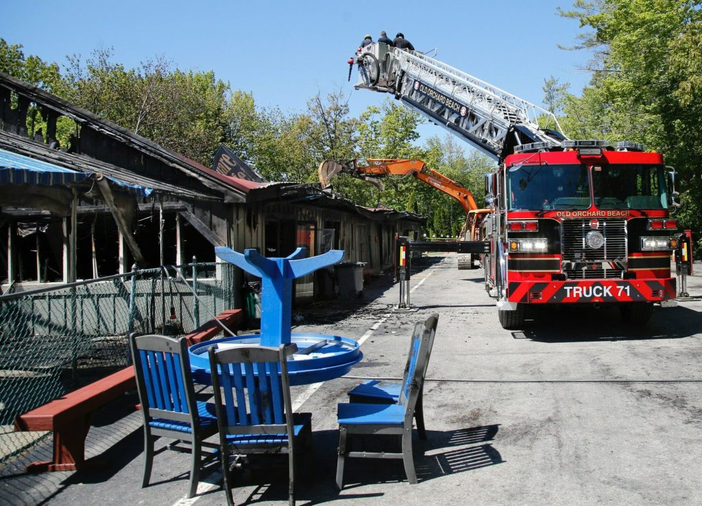 Fire investigators inspect the burned building at Bayley's Camping Resort in Scarborough on Wednesday as an excavator peels back the metal roof.