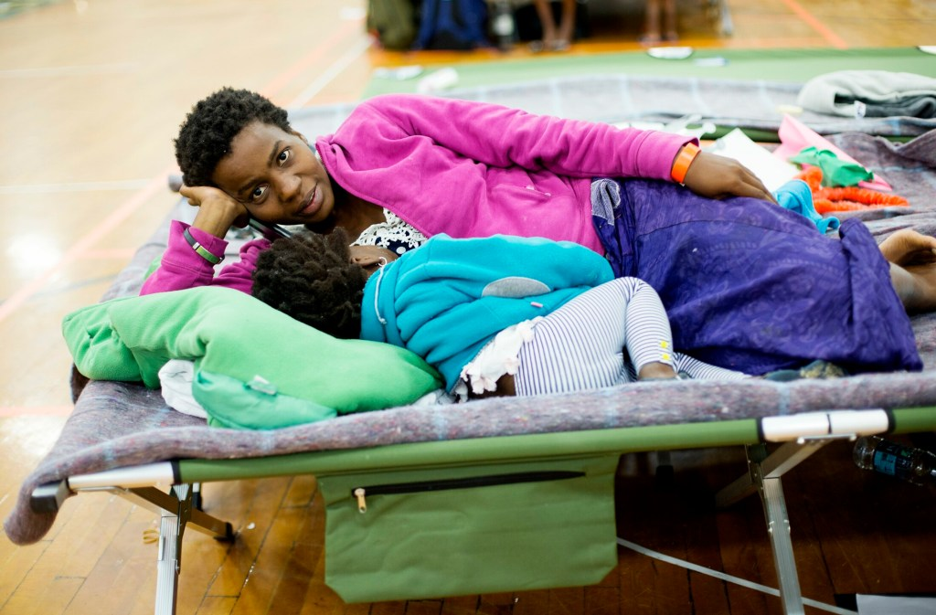 Sofia Ida of the Democratic Republic of the Congo rests with one of her children at an emergency shelter for asylum seekers at the Portland Expo. Ida, who is pregnant, came to Portland with her two children and her husband after fleeing from the Congo to Brazil.