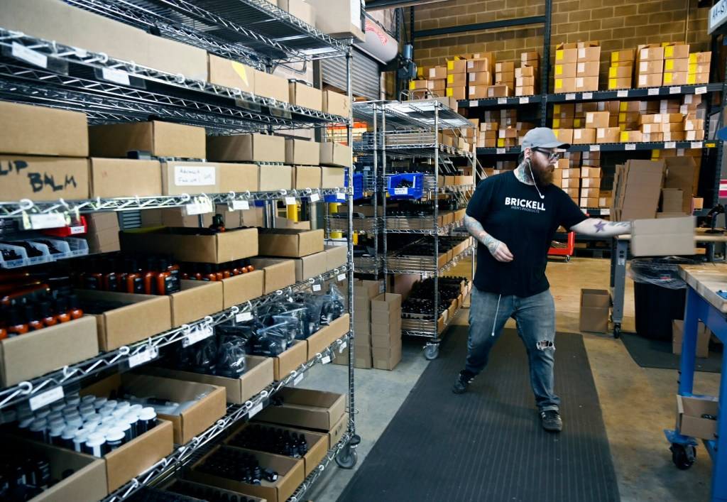 Tim Bell packages products for shipping at the Brickell Men's Products warehouse in Portland. The company, started by two Skowhegan natives, reported sales of $10 million last year, and is poised to double that this year.