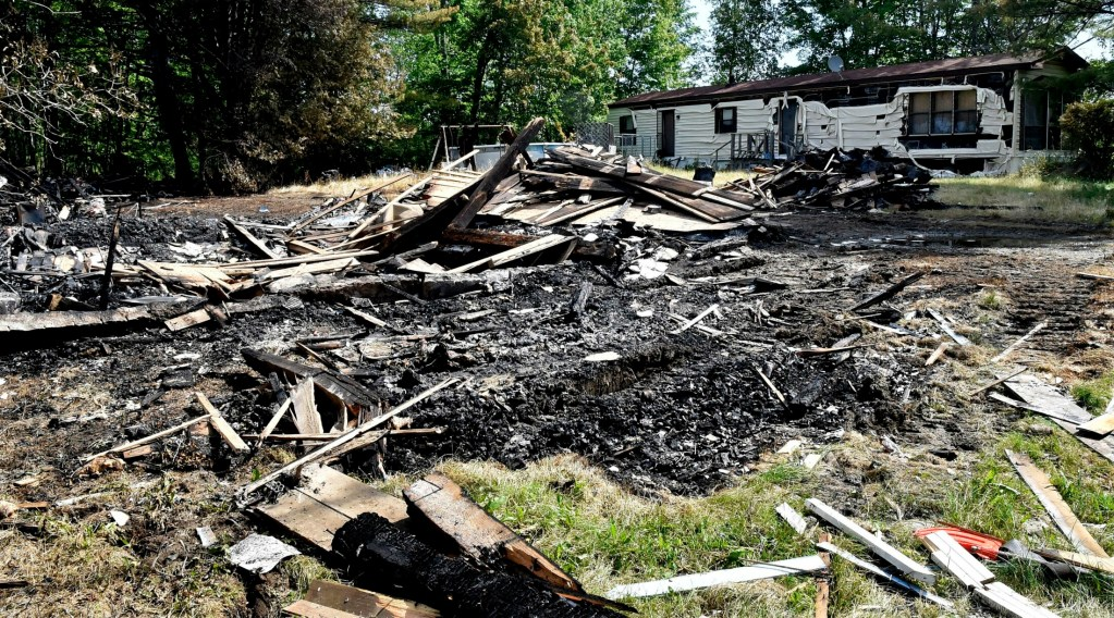 On Tuesday, a pile of burned wood and home furnishings is all that remains of a home along U.S. Route 2 in Palmyra that was destroyed by fire Sunday.