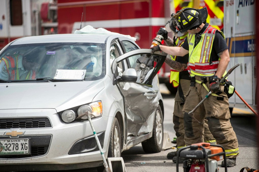 Waterville firefighters extract Alexis Hewey, 23, from her car after it and another car collided Tuesday on College Avenue in Waterville.