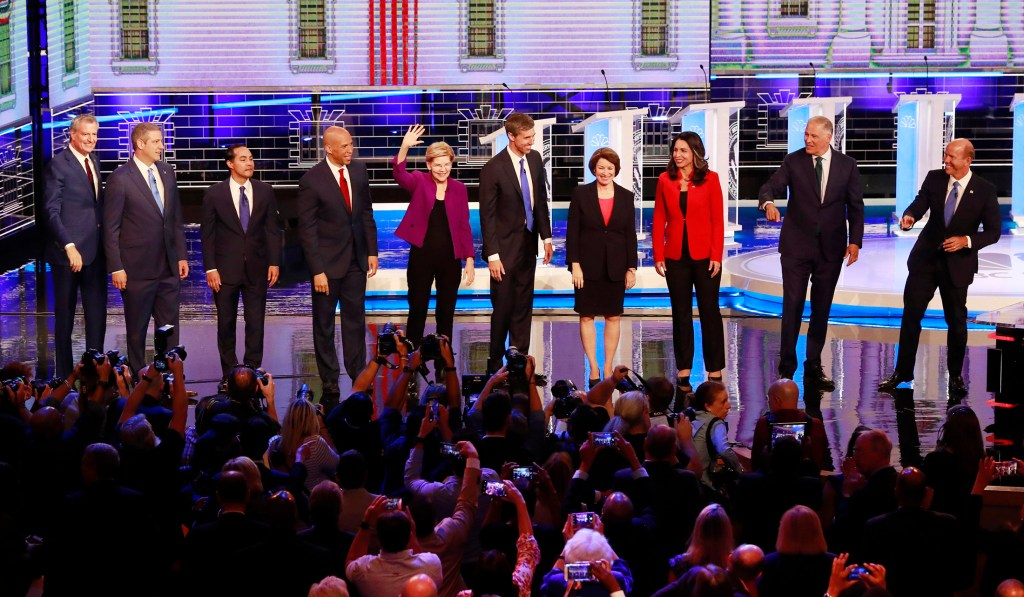 From left, New York City Mayor Bill de Blasio, Rep. Tim Ryan, D-Ohio, former Housing and Urban Development Secretary Julian Castro, Sen. Cory Booker, D-N.J., Sen. Elizabeth Warren, D-Mass., former Texas Rep. Beto O'Rourke, Sen. Amy Klobuchar, D-Minn., Rep. Tulsi Gabbard, D-Hawaii, Washington Gov. Jay Inslee, and former Maryland Rep. John Delaney pose for a photo on stage before the start of Wednesday's Democratic primary debate hosted by NBC in Miami.
