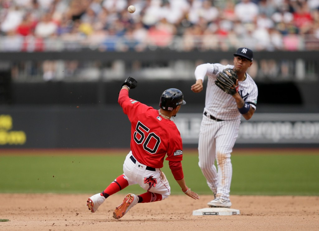 Boston Red Sox's Mookie Betts, left, is forced out at second by New York Yankees second baseman Gleyber Torres after Xander Bogaerts hit into a double play during the fifth inning of a baseball game in London, Sunday, June 30, 2019. (AP Photo/Tim Ireland)