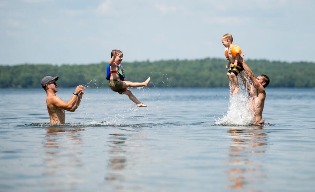 Cory Gooldrup, left, tosses his son Ayden, 3, as his Cory Gooldrup's brother, AJ Gooldrup, right, throws his own son, Noah Gooldrup, 3, as they escape from the heat Saturday in East Pond in Oakland.