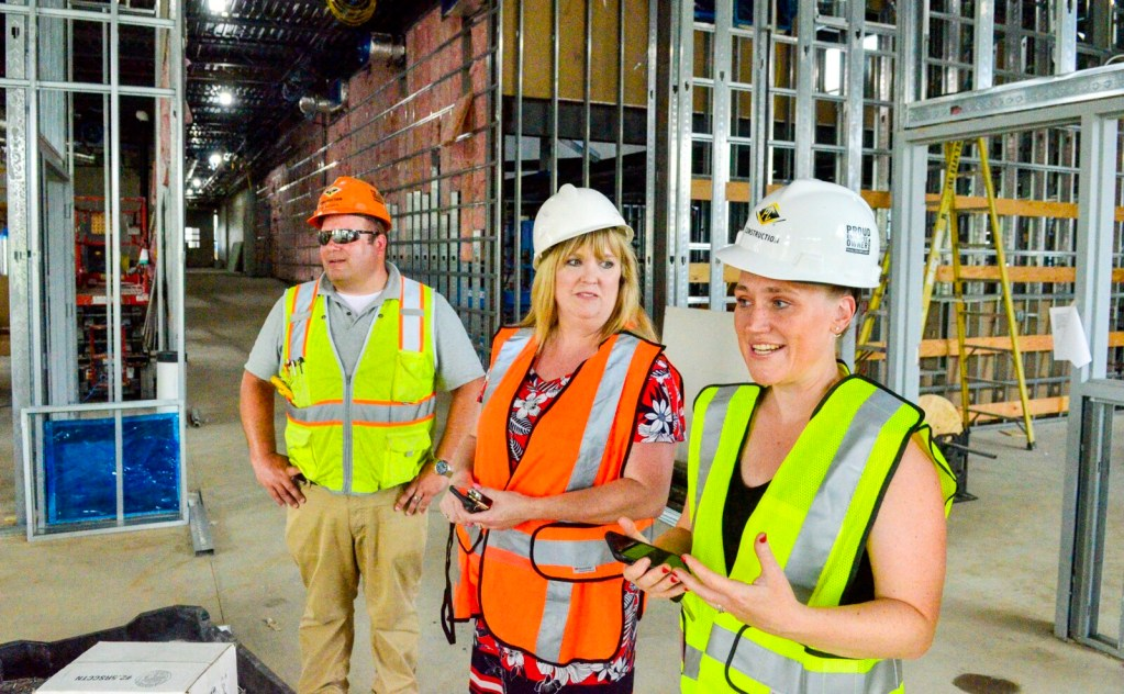 Principal Mel Burnham Barter, right, RSU 2 Superintendent Cheri Towle, center, and construction Superintendent Grit Richards, of PC Construction talk about the library Wednesday during a tour of Monmouth Memorial School, the new pre-K to 8th grade school being built in Monmouth.
