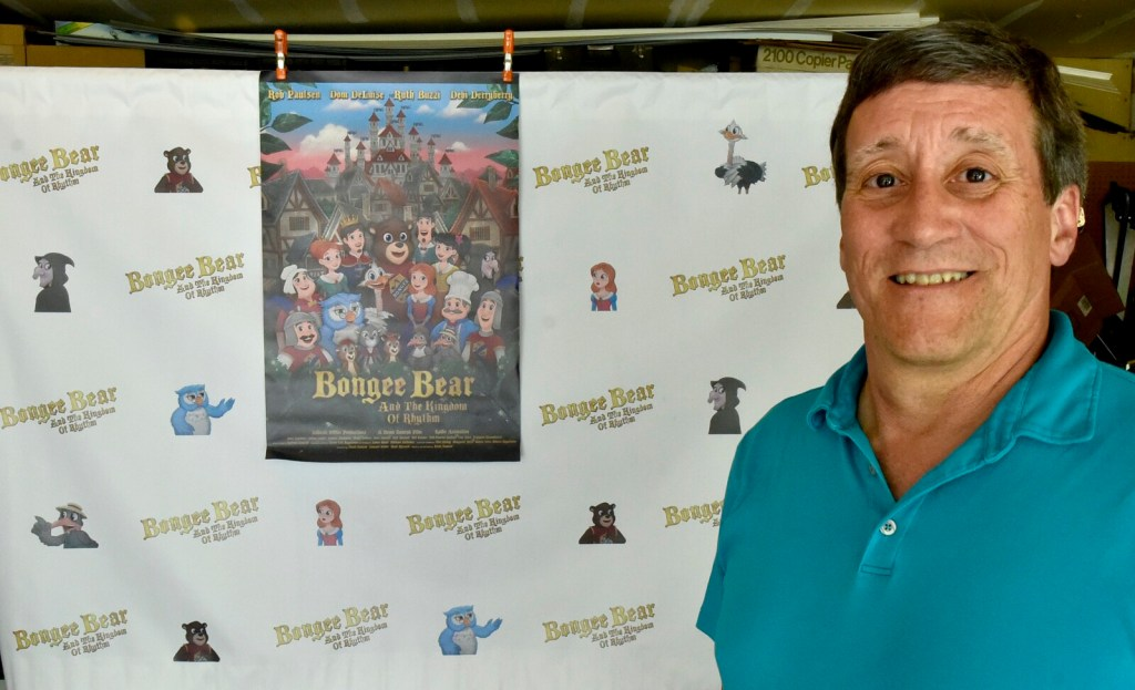 """Filmmaker Brian Zemrak, of Winslow, poses on Thursday before a wall hanging and poster of his animated movie, """"Bongee Bear and the Kingdom of Rhythm."""" The movie will premiere Saturday during the Maine International Film Festival."""