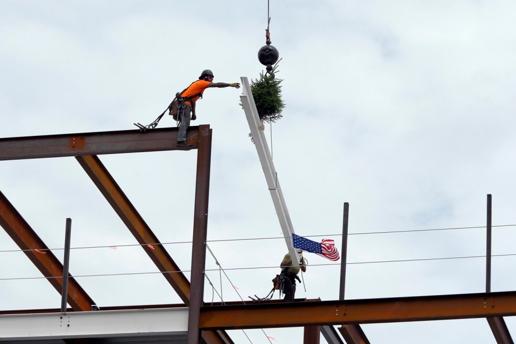 Sean Nolan, left, and Nick Andrews of Bouchard Steel Erectors lay the final beam on the main structure of Hobson's Landing on Wednesday. The project is being built on the former site of Rufus Deering Lumber Co. on Commercial Street in Portland. The beam was adorned with a traditional pine tree for good luck and an American flag.