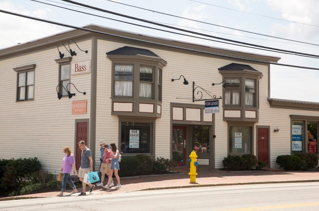 Shoppers walk past a retail space for lease on Main Street in Freeport. Both Kittery and Freeport have seen sales declines in the past five years, prompting some new initiatives to deal with that impact.