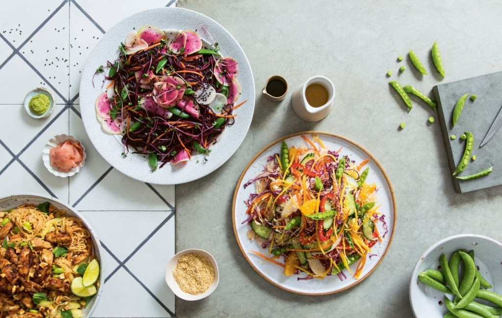The Peanut & Sticky Chili Chicken Rice Noodles salad is pictured on the far left.